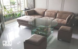 Unique 016: Tempered glass round coffee table with square raise up tank as the table stand. Made from 12mm all clear glass. Size 600mm (L) x 600mm (W) x 600mm (H). Diameter 1000mm Table Top x 12mm clear tempered glass with CNC.